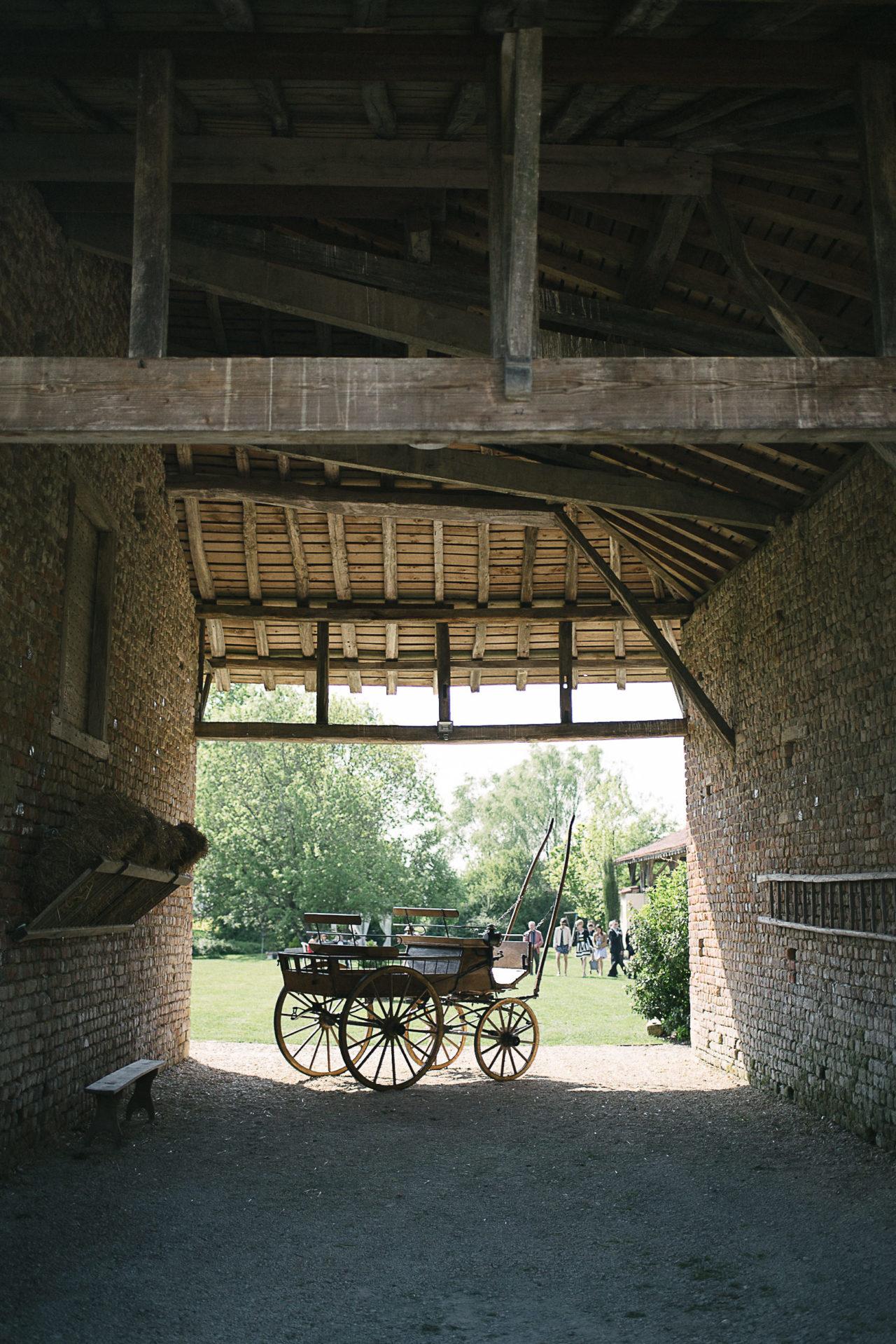 La réception de mariage a lieu dans une vieille ferme, en témoigne cette charette