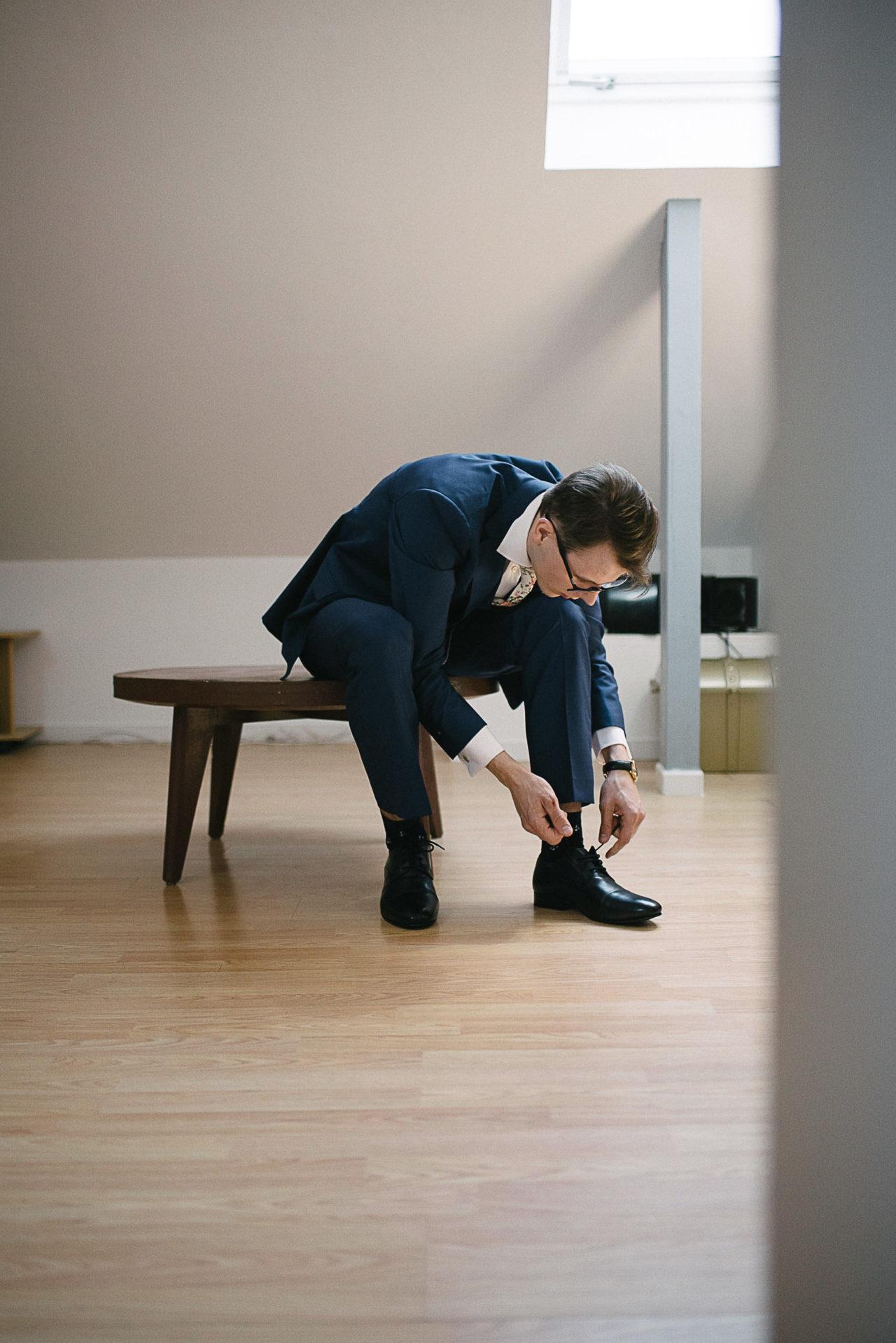 Le marié finit de lacer ses chaussures avant de retrouver sa future femme